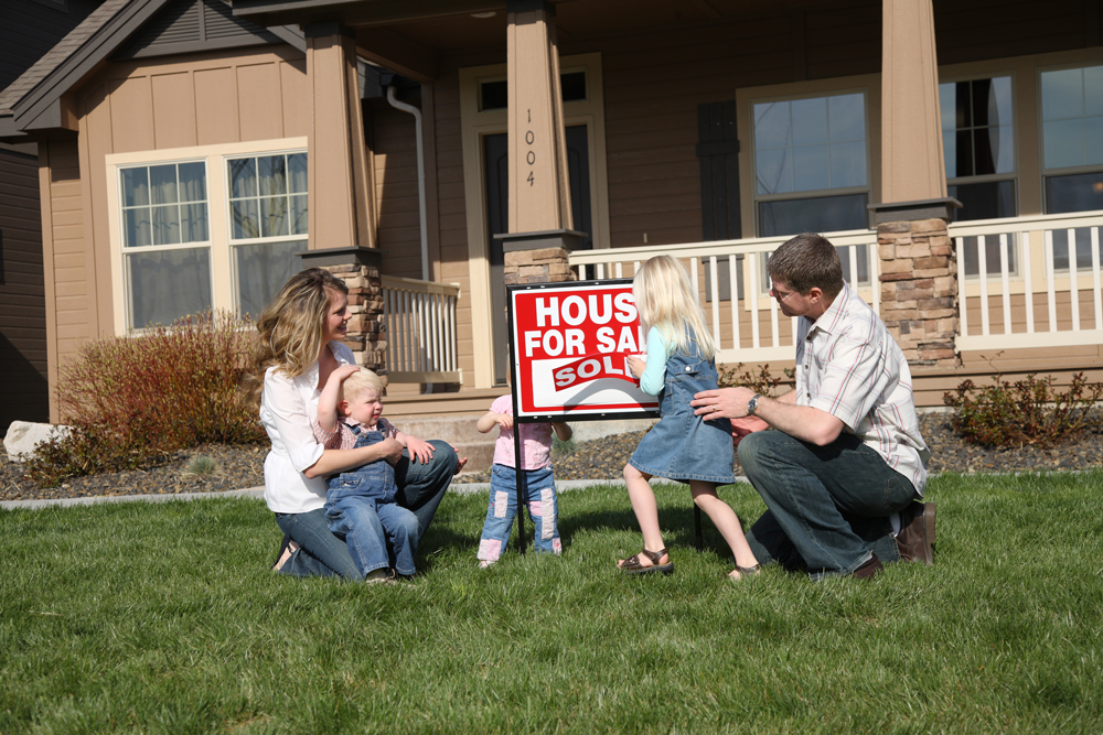 Young Family in Front of Home for Sale